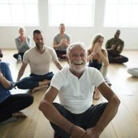 Group of people sitting and doing yoga