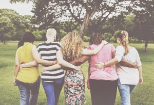 Diverse group of women with arms around each other
