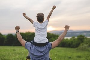 Dad with arms in the air and his son sitting on his sholders