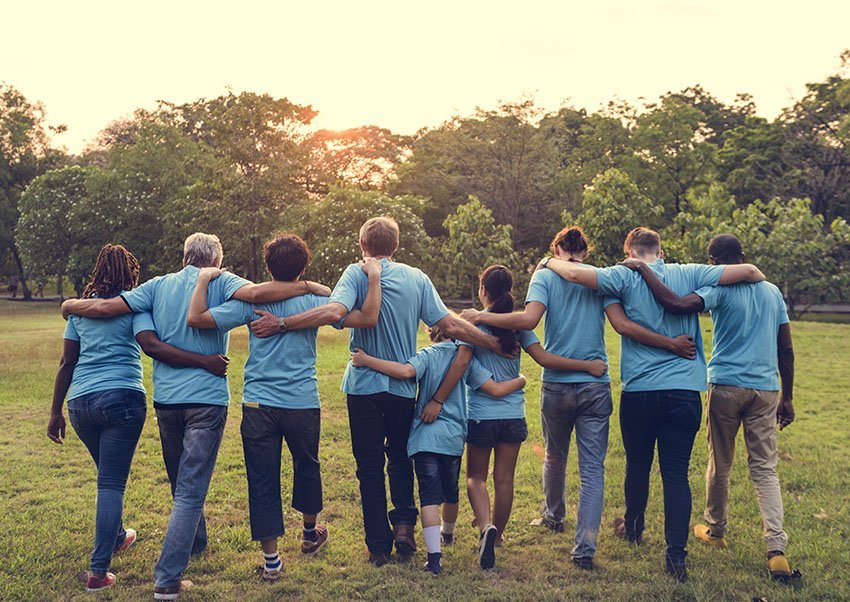 Group of people in blue shirts with arms around each other